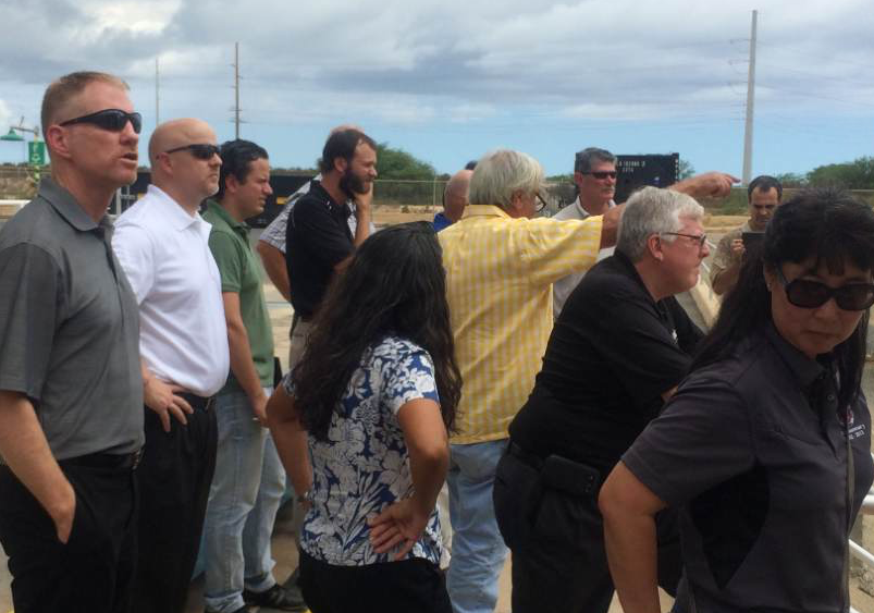During a tour of Asphalt Hawaii's Kalaeloa Asphalt Terminal, the company's president, Richard Levins, pictured here in the center in the yellow plaid shirt, pointed out specific items to the tour participants. Levins is also the president of HAPI.