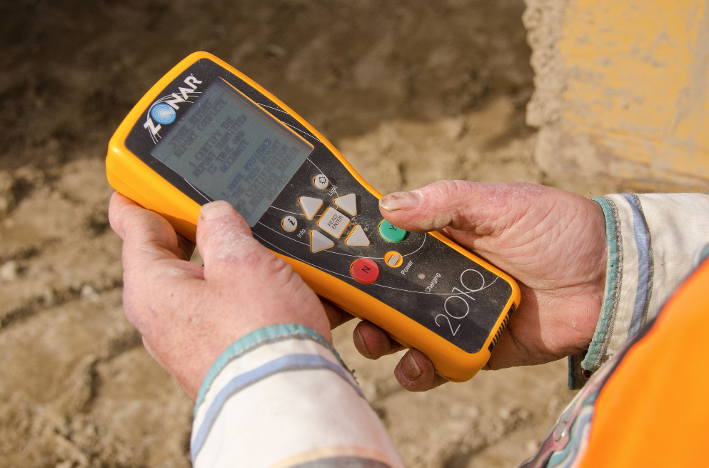 "To use the system, RFID tags are placed on the piece of equipment at critical inspection points. These are called ""zones."" When the equipment operator approaches the vehicle for the day's shift, he turns on the handheld Zonar 2010™ EVIR reader, pictured here, which is also called the inspection tool. He holds the reader close to the RFID tag at each inspection zone."