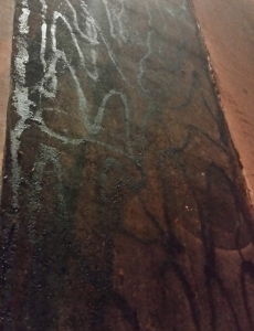 This tack has been poured from a melter by hand and is streaked across a small section of pavement in a haphazard manner. Don't use this method of tacking and expect a good bond between a thin overlay and the existing surface. Photo courtesy Sandy Lender.