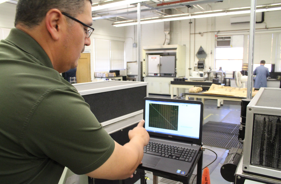 Asphalt Lab Supervisor Jesus Barajas demonstrates a typical graph showing the rutting depth of a gyratory compacted specimen.
