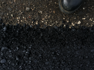 This picture shows the difference in the conventional mix, with the worker's boot, and the treated crumb rubber asphalt mix. Photo courtesy Liberty Tire Recycling.