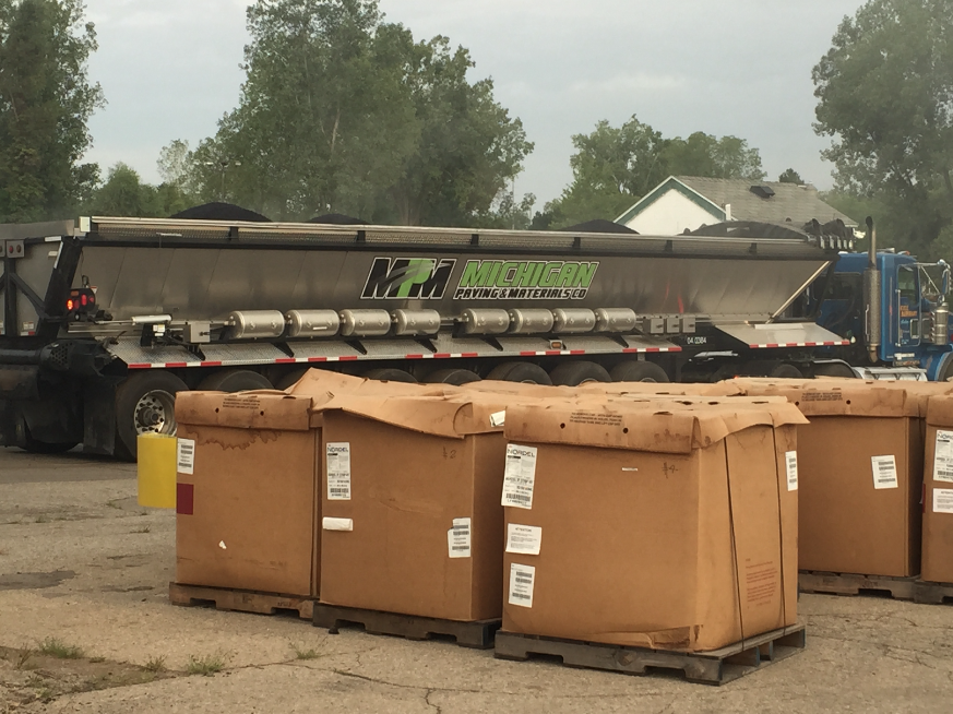 With the plant running about 300 TPH and the Mix Maxer added at about 10 pounds per ton, the team used about 3,000 pounds of Mix Maxer an hour, or 50 pounds per minute. The Mix Maxer was packaged in 1,000-pound Gaylord boxes. Photo courtesy Liberty Tire Recycling.