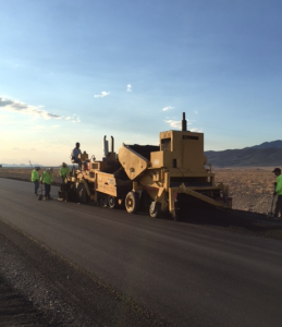 The Wulfenstein paving crew paves in Death Valley in the summer of 2016. Despite the heat, the crew wears long-sleeved shirts, and many of them are wearing hats to protect themselves from the sun.