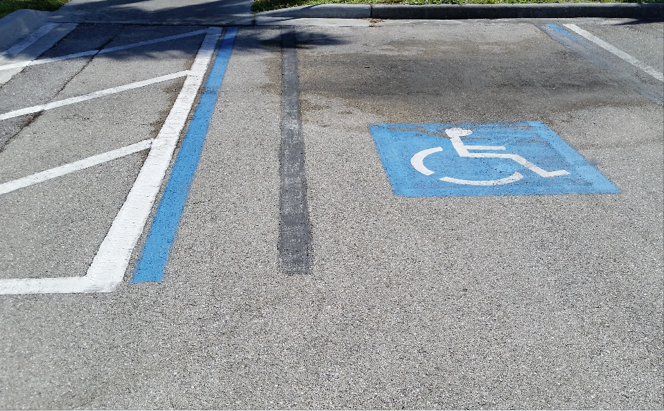 At a post office in southwest Florida, you can see where the team had to re-lay out the row of parking spaces to accommodate the increased number of ADA spaces required for the size of lot this business has. When the crew has to restripe for any reason, the use of black paint or sealer can cover the old markings, or someone may need to use a pavement scarifier to grind paint off the surface.