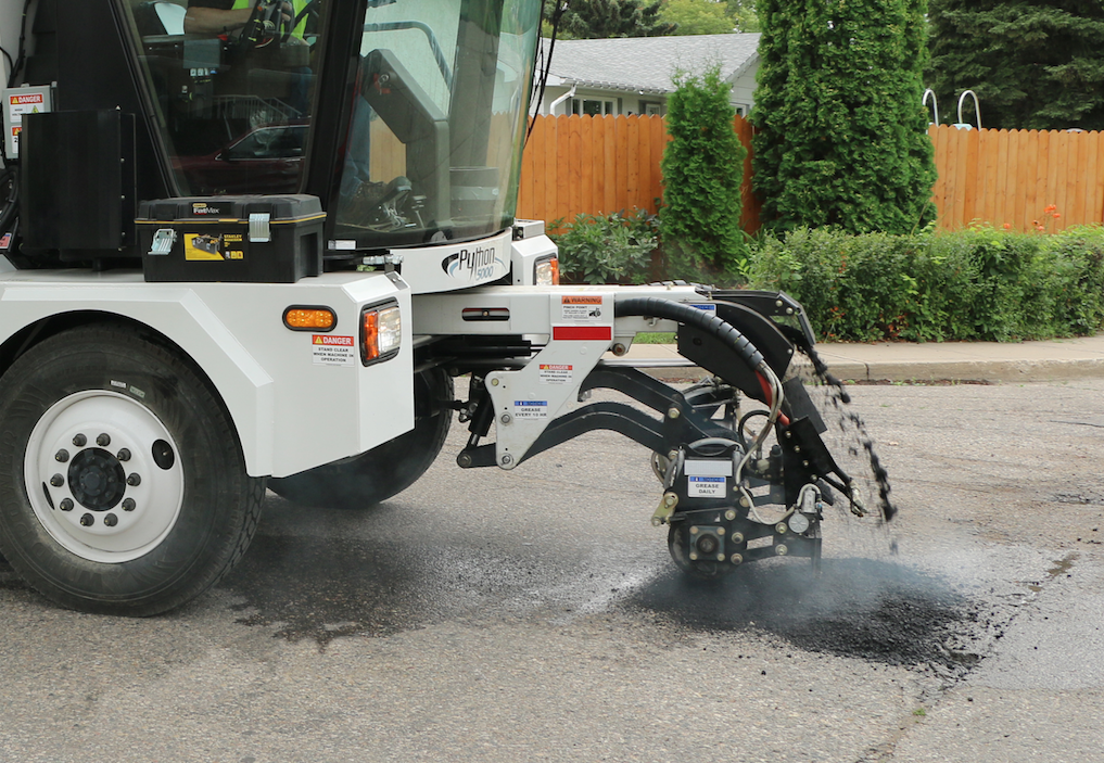 """With SuperiorRoad's Python 5000 pothole patcher, the operator can complete each step of the process without leaving the cab. """"The operator drives the machine up to the hole, blows it with air blasts of 120 PSI,"""" Yaskinski said. """"The second stage is the application of tack oil."""" The hopper will heat the material, which is then augered onto the belt and delivered into the hole. The operator can then rake the mix for even distribution and then compact with the Python 5000, which offers the same force as a 1-ton roller. Photo courtesy of SuperiorRoads Solutions."""