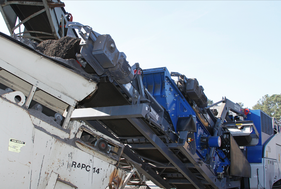 The conveyor-mounted screen eliminates the need for a stand-alone screen, contributing to a compact footprint that lets the impactor sit within the hot-mix plant layout.