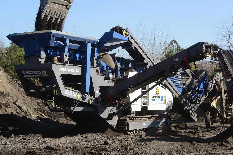 For C.W. Matthews, the Mobirex crusher is fed by an excavator rather than a front end loader. Fines off prescreen (center) bypass the crushing circuit and are conveyed to a super stacker where they rejoin half-inch minus material.