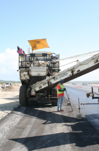 The crew delivers material to the paver in such a way that they keep heavy equipment off the tack coat at the South Caicos International Airport.