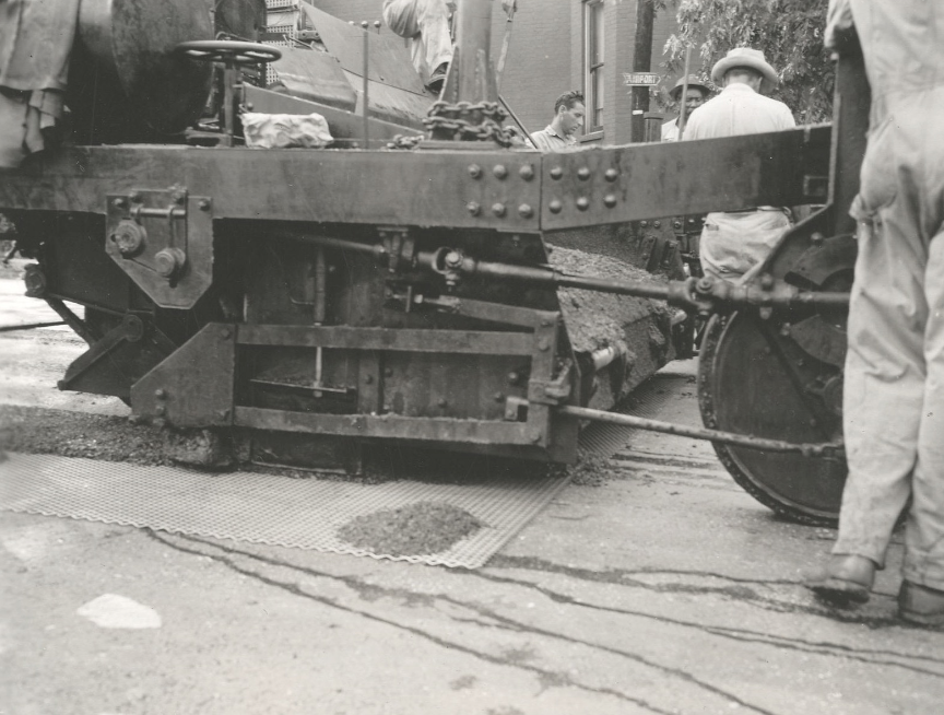 At the intersection of Third and Jefferson in August 1947, a hard-working crew placed shovelfuls of mix atop an interlayer to hold it in place for paving. Then motorists drove on the mat the roller operators were trying to compact.