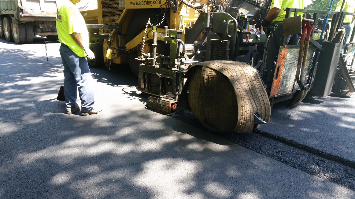 The screed operator uses a lever to spray the Notch Wedge Pneumatic Roller tire with release agent from the roller's pressurized tank.
