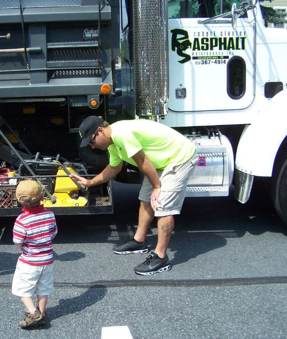 RS Asphalt Maintenance donates its dump truck for the Elizabethtown Public Library's annual Touch a Truck event, giving children of the community an opportunity for an up-close and personal look at various trucks. Here, Casey explains to a curious youngster how the tamper works.