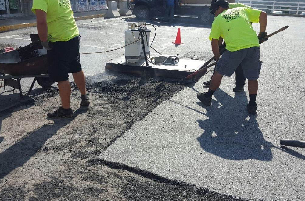 The RS Asphalt Maintenance team uses the infrared heater to remove old asphalt and replace with a fresh mix.