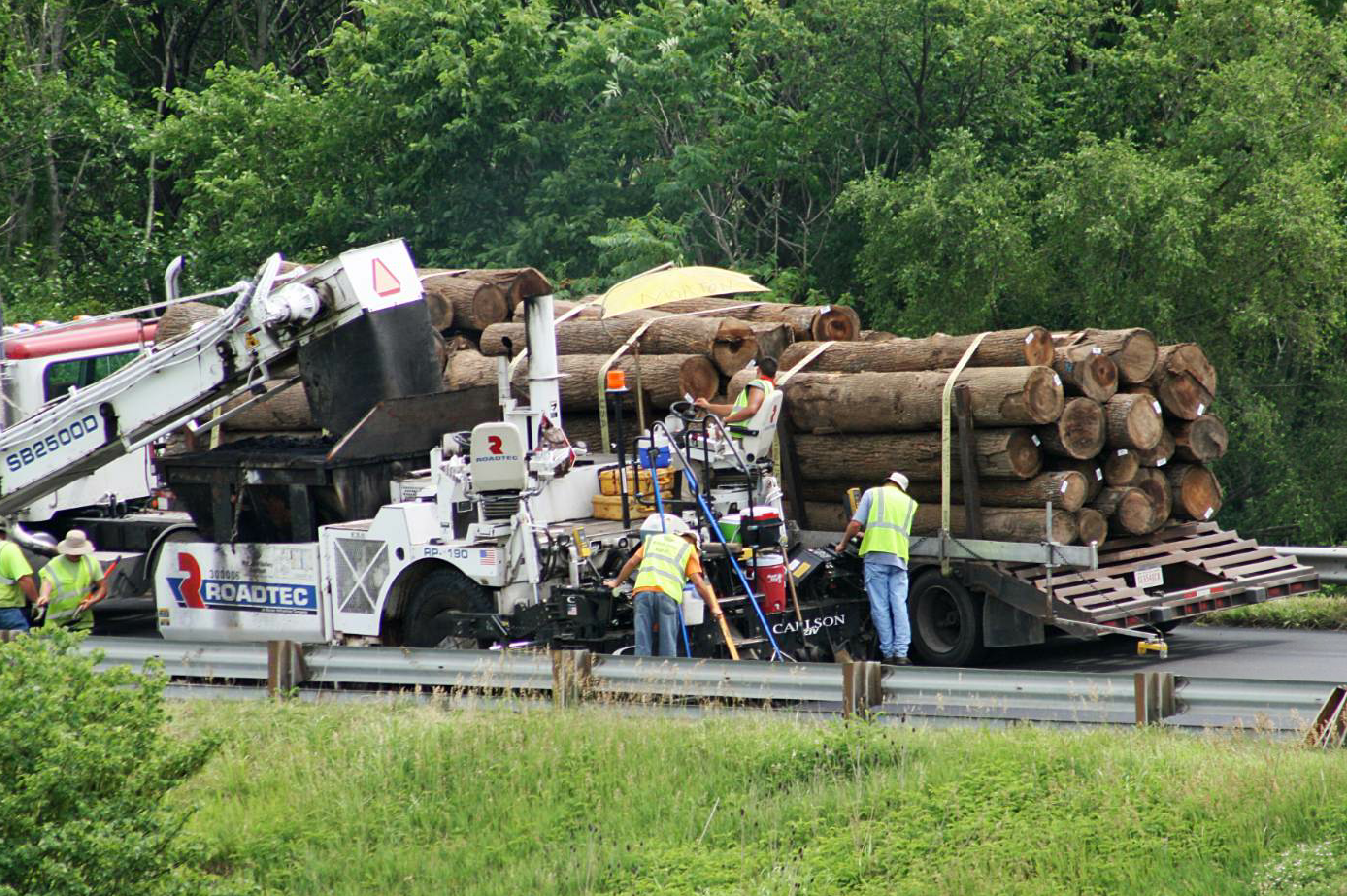 Wabash Valley's crew paves in close quarters with a wide load on a two-lane road.
