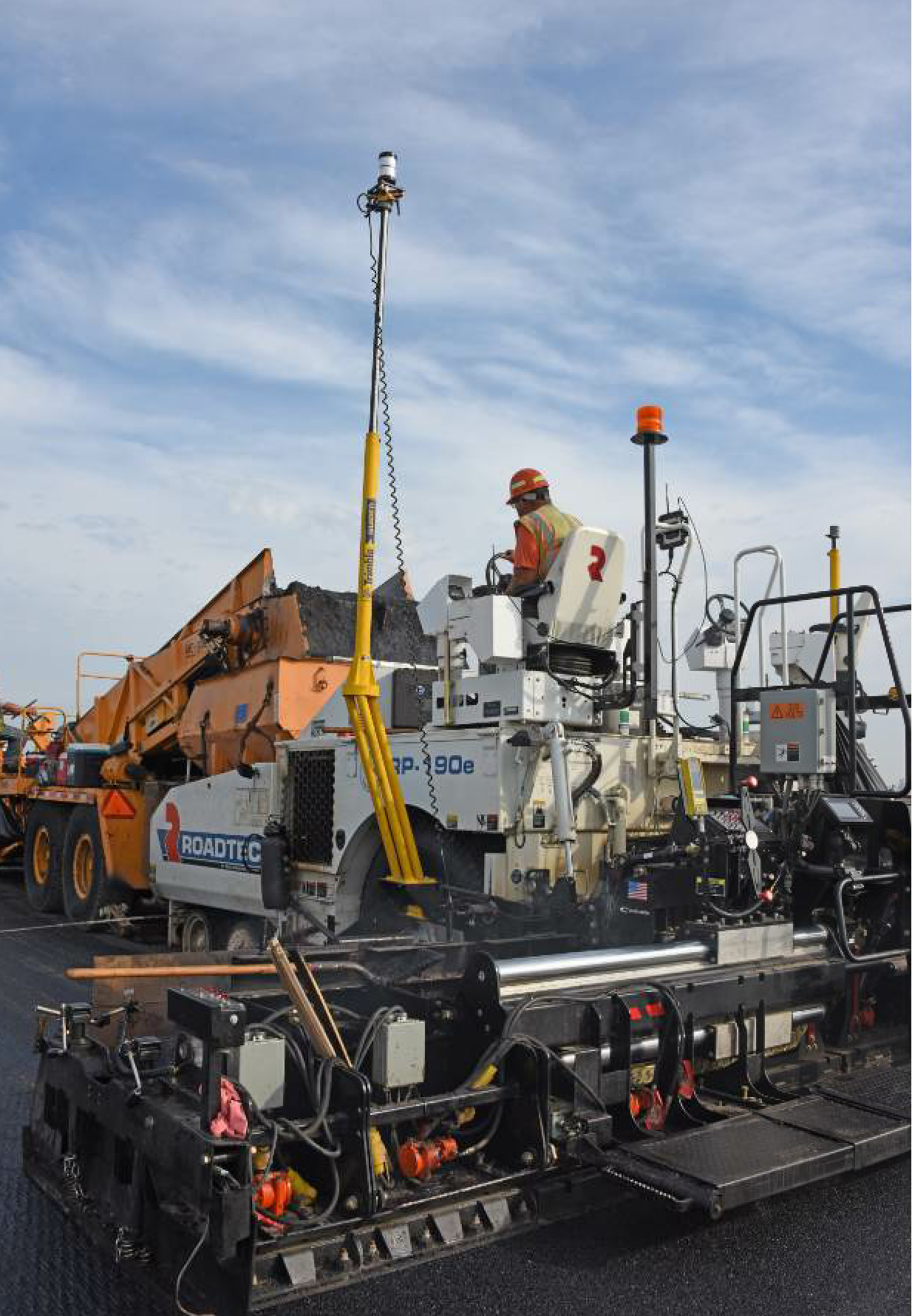 The Trimble 3D Paving PCS900 Control System included the Universal Total Station on-site with the mast-mounted target on the tow arm of the paver with a Trimble MT900 prism on top and a slope sensor. A Trimble CB460 control box displays the 3D design model and the position of the screed.