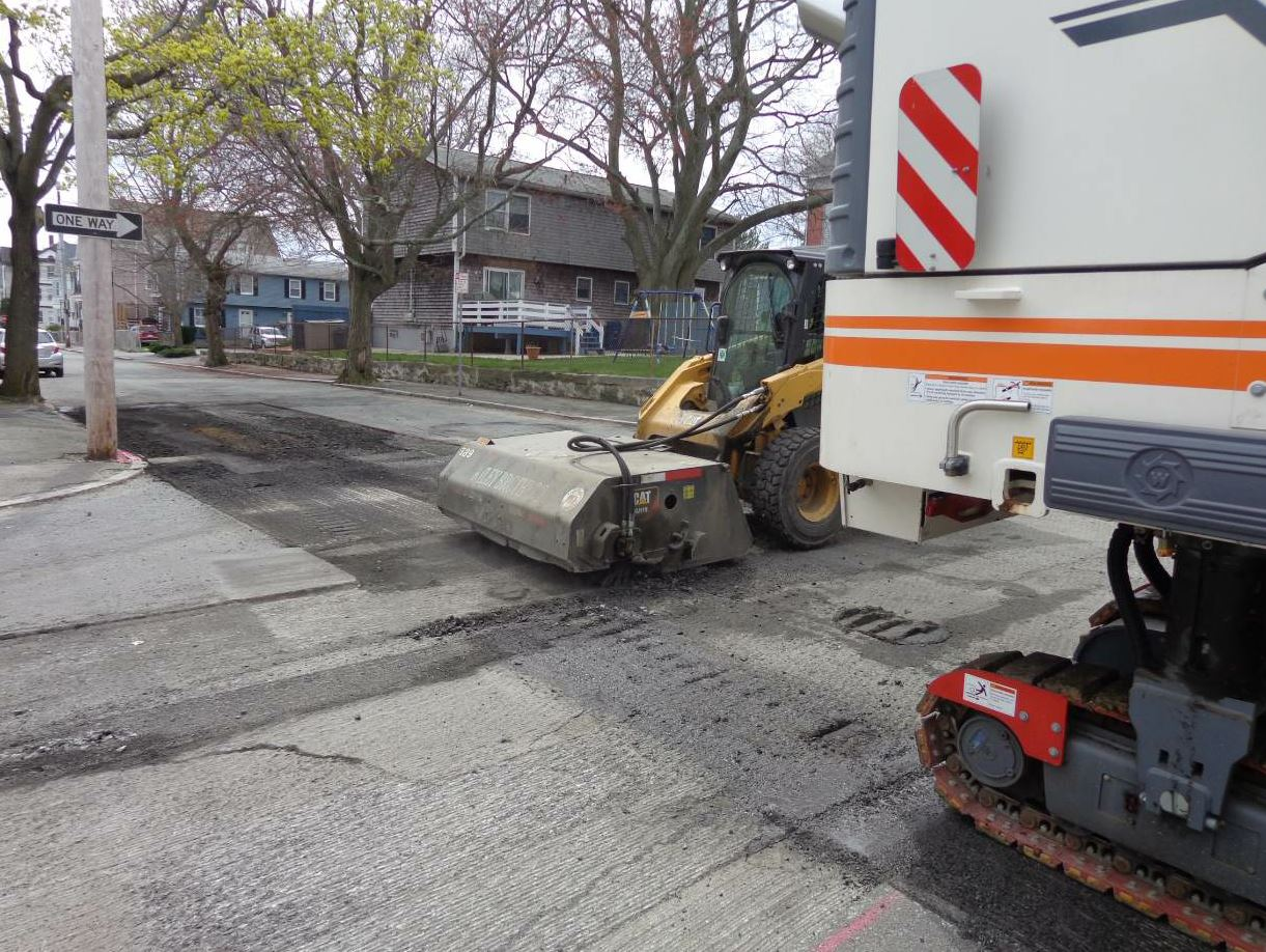 The broom on the city street may require a system to capture material and dust. This skid steer will routinely empty the bucket of millings into a waiting truck body.