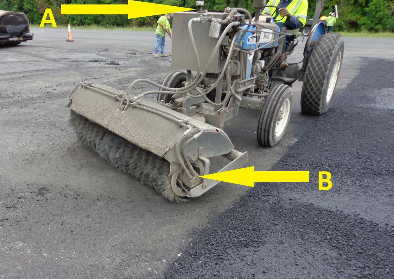 "Letter A indicates the need to maintain the lights on the broom. When you're sweeping, you have the potential to kick up dust. When on a roadway or even working around new employees in a commercial lot, drivers may not realize ""what"" they are driving up on as they near something dusty. Strobe lights, four-way flashers and other construction vehicle lights alert the general public, haul truck drivers, subcontractors and others to your presence, no matter the level of dustiness. Letter B indicates the hydraulic lines that deliver the ""power"" that turns the drum. Check this area before the shift begins to make sure there's no build-up of dirt or pollution that will interfere with the machine's operation. Notice that the broom is set at a 33 degree angle to clean the surface prior to its next treatment. All photos courtesy John Ball of Top Quality Paving and Training, Manchester, New Hampshire."