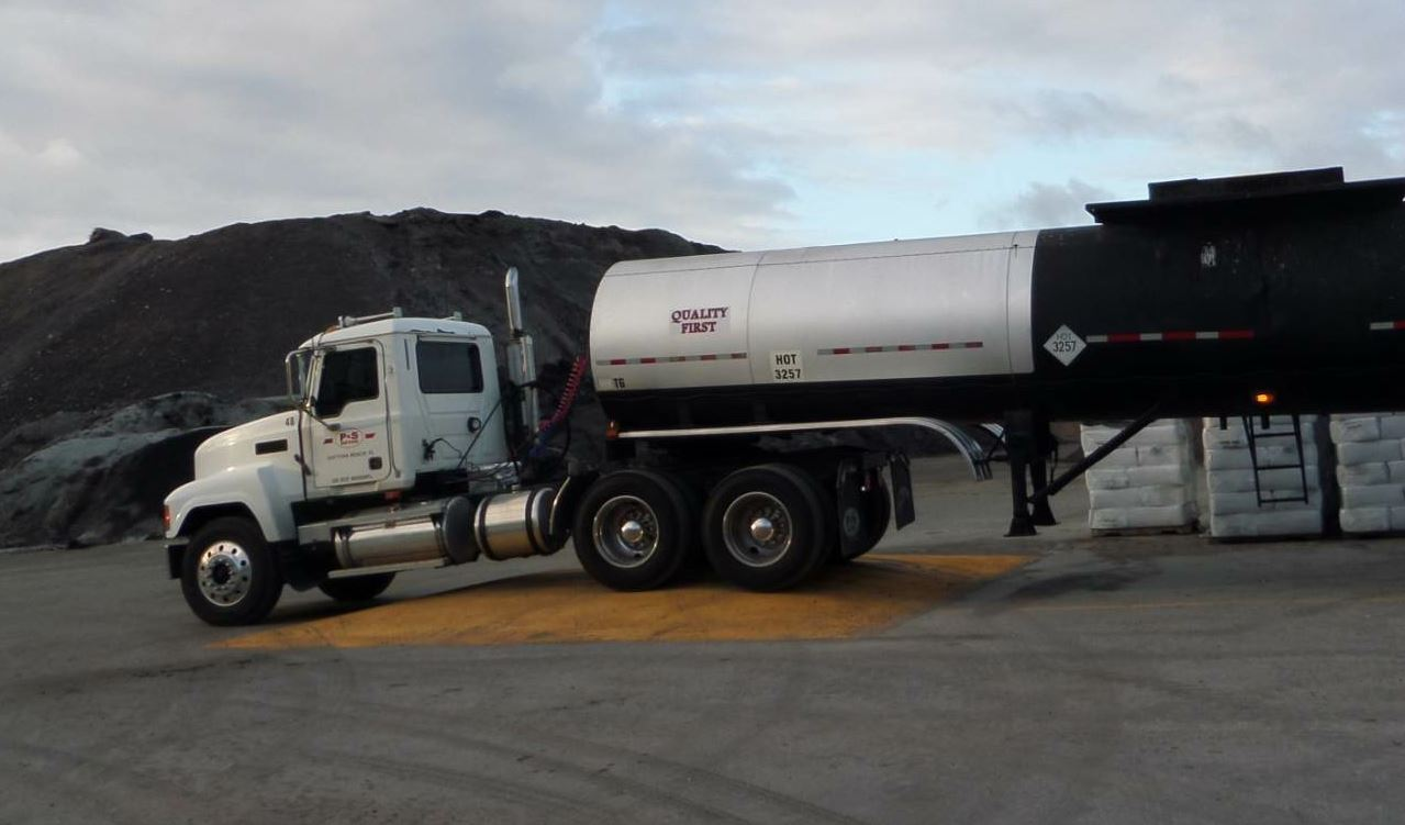Gravity—it's not just a good idea, it's the law. P&S Paving Company puts gravity to work even when receiving liquid material. Notice this driver has the front end of the tanker on the 18-inch high tanker offloading island so the material flows downhill, making the pump's job a little easier.