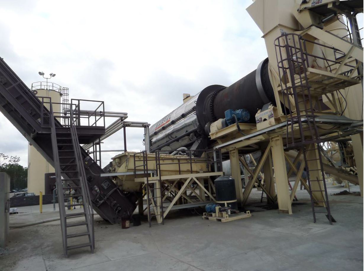 The Double Barrel drum from Astec feeds the twin pugmill (center), which mixes the dried, heated aggregate with incoming, metered hot liquid binder, and then sends the mix up the conveyor to the silo.