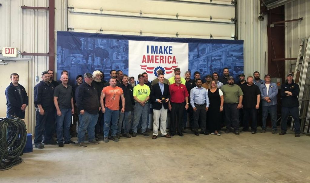 "U.S. Representative Jim Banks poses for a group photo with employees at ADM's facility in Huntertown, Indiana. ADM invited the congressman through the AEM ""I Make America"" program. Photos courtesy Asphalt Drum Mixers."