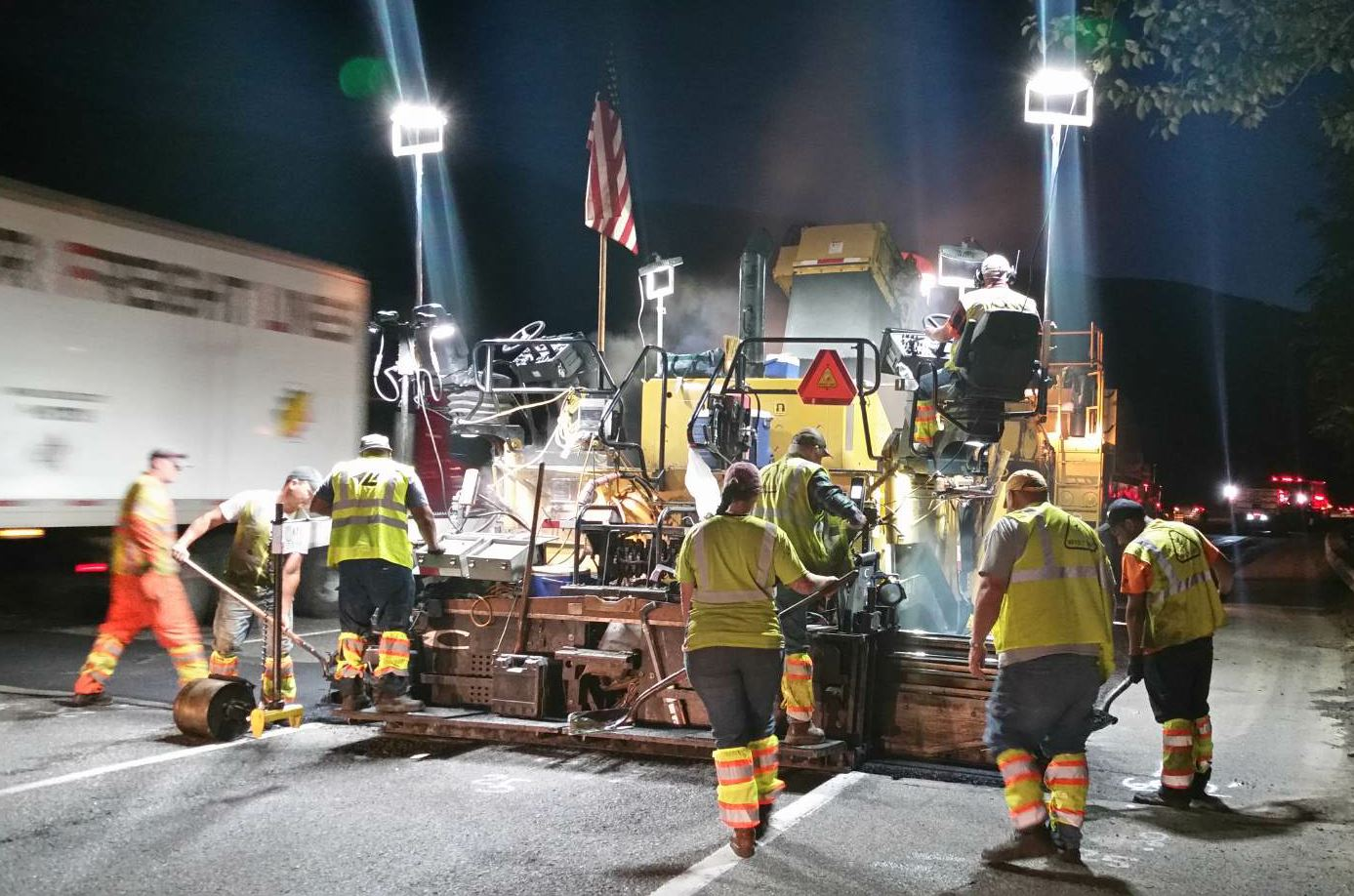 Getting down to business, the crews from Lakeside learn to be the best pavers they can be. Here a crew participates in night paving of westbound I-90. Check out the compaction wheel getting initial density as they build the joint.
