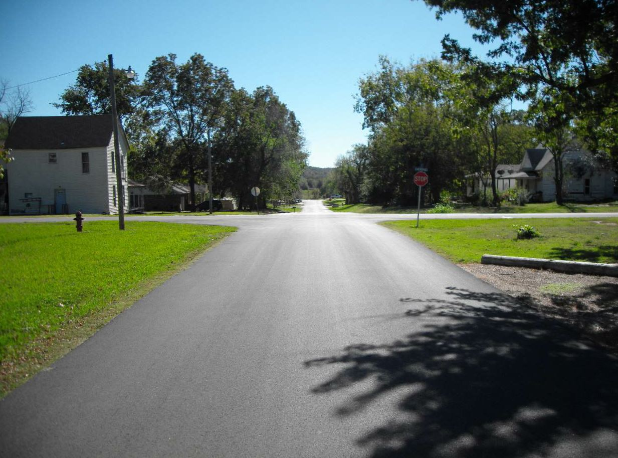 When a shade tree casts a shadow over the pavement, the crew must modify the rolling pattern to get proper compaction of the mat. Dunham's Asphalt Services has trained the team to get the leaves and debris out of the way and to make adjustments for rolling. This image is from their award-winning overlay in the City of Cleveland.