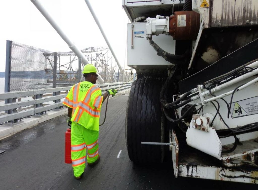 This worker sprays a release agent on the material transfer vehicle (MTV) tires. Even though the MTV is working in the lane beside the paving lane, you don't want it to collect dribbled mix or stray material on its tires. Keep the machine moving smoothly.