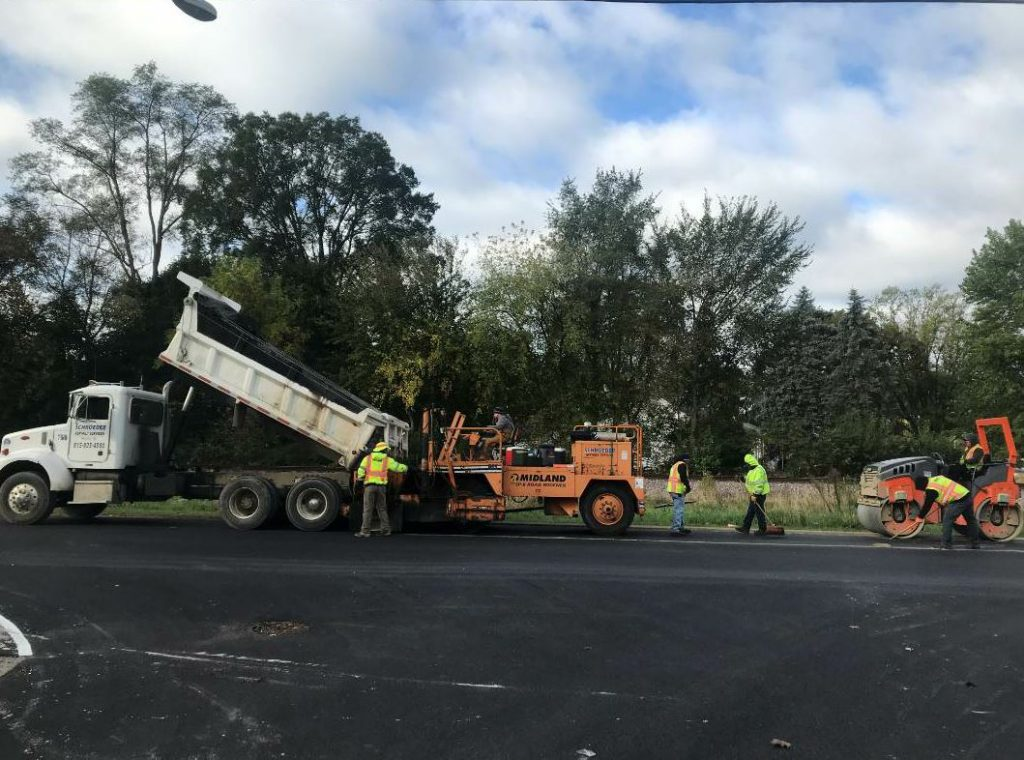 """The Midland road widener was bought brand new about 7 years ago,"" Brent Schroeder said. ""We use this on many 7-foot or under asphalt or gravel installations."" This picture shows the crew using the Midland on a City of South Elgin project in 2018. ""We were installing a 3-foot-wide gravel shoulder next to the newly paved road. This is a great machine and can be used for many aspects in our industry. We like it because it's smaller than a Blaw Knox, which lets us get down narrow streets or tight areas and has the ability to get up and over the curb for those projects that have paving or aggregates behind the curb. This machine is user friendly and can be used to put down a lot of material with a small crew. Our employees love it when we can use this machine instead of the shovel!"""